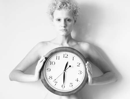 black clock hands: Sensitive curly girl with big clock in hands. Black and white photo.