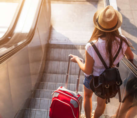 travel: 年輕的女孩與手提箱下來扶梯。 版權商用圖片