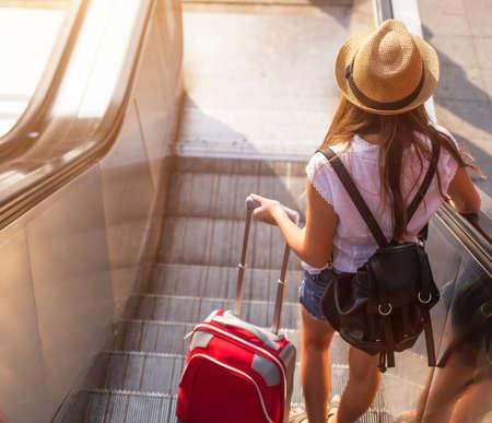 Mladá dívka s kufrem dolů eskalátoru. Reklamní fotografie