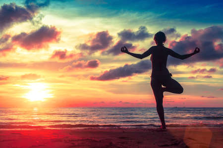surrealistic: Silhouette young woman practicing yoga on the beach at surrealistic sunset. Healthy lifestyle choices.