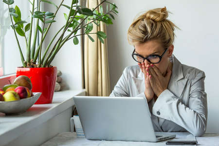 Shocked young businesswoman looking in her laptop, by covering mouth with hands.
