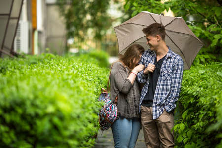 cute guy: Cute guy and girl talking under an umbrella.