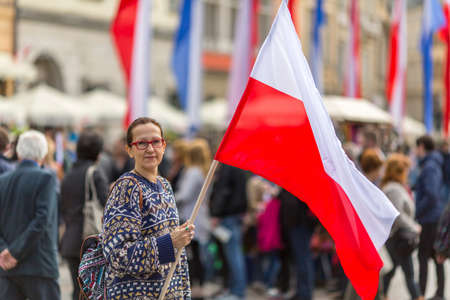 Polonia: Woman on the street holding a flag of the Republic of Poland.