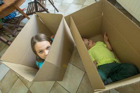 Los niños se sientan en cajas de cartón. Desembalaje de cuadros y pasar a un nuevo hogar. Concepto estreno de una casa.