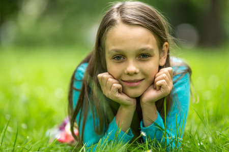 nine year old: Close-up portrait of a nine year old girl lying in the green grass.