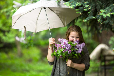 lilacs: Teen girl with a bouquet of lilacs, standing under an umbrella in the garden. Stock Photo
