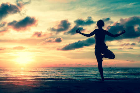 beach yoga: Silhouette of a beautiful yoga woman at amazing sunset in surreal colors.