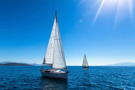 sailing: Sailing yacht race. Ship yachts with white sails in the open Sea. Luxury boats. Stock Photo