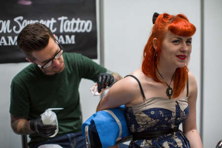 tattoo arm: KRAKOW, POLAND - JUNE 6, 2015: People make a tattoos at the 10-th International Tattoo Convention in the Congress-EXPO Center. This year anniversary TattooFest is tattoo Studio with an area of 2000m2. Editorial
