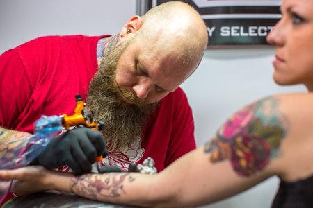 alzando la mano: CRACOVIA, Polonia - 06 de junio 2015: La gente hace un tatuaje en la 10 ª Convención Internacional de Tatuaje en el Centro de Congresos-EXPO. Esta TattooFest aniversario es Estudio de tatuajes con una superficie de 2000m2.