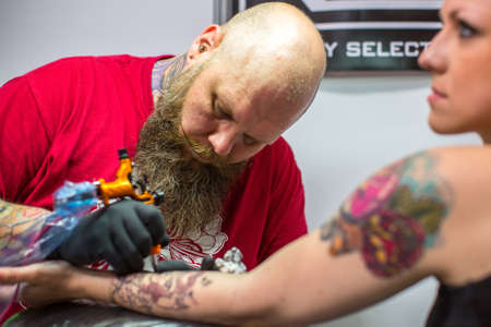 arm tattoo: KRAKOW, POLAND - JUNE 6, 2015: People make a tattoos at the 10-th International Tattoo Convention in the Congress-EXPO Center. This year anniversary TattooFest is tattoo Studio with an area of 2000m2. Editorial