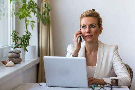 Young beautiful business woman talking on the phone while sitting with a laptop.