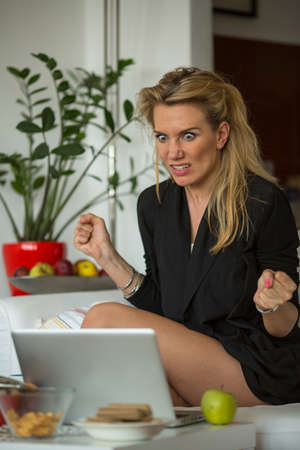 irritated: Nervous irritated young woman sitting in front of a laptop. Stock Photo