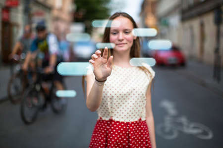 finger teen: Young cute teen girl in the street presses an imaginary button in the air. Buttons with place for your text.