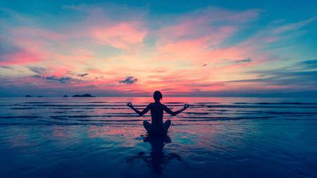 Vrouw die meditatie doen dichtbij het oceaanstrand. Yoga silhouet.