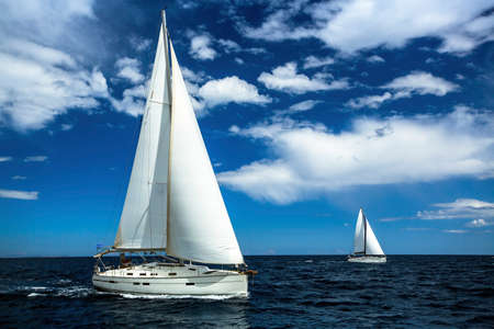 sailing: Ship yachts with white sails in the open sea. Sailing. Yachting. Luxury Lifestyle. Stock Photo