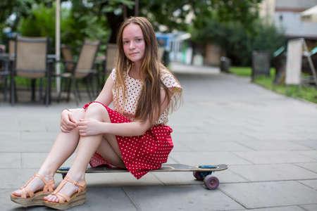 patín: Muchacha adolescente linda que se sienta en una patineta en la calle. Foto de archivo