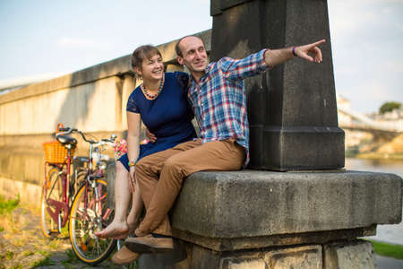 passionately: Happy young family. Couple in love sitting on the curb embankment and passionately talking.
