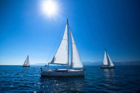 Zeilschip jachten met witte zeilen in de open zee. Noon, de blauwe lucht en de zon op de Zenith.