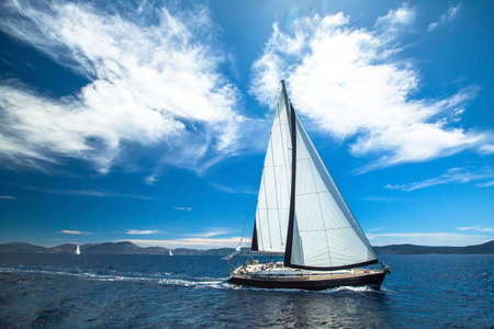 ship bow: Sailing ship yachts with white sails in the open Sea. Luxury lifestyle. Stock Photo