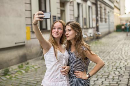 niñas sonriendo: Dos adolescentes lindos toman selfie en un teléfono inteligente en la calle del barrio antiguo de la ciudad. Foto de archivo