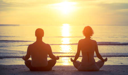 tropical beaches: Silhouettes of a young couple sitting in the yoga Lotus position on the banks of the sea during sunset. Stock Photo