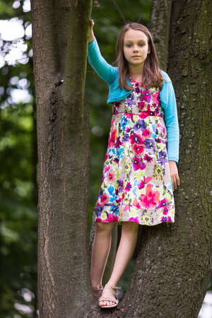 girl in full growth: Portrait in full growth of little girl stands on the branches of a tree.