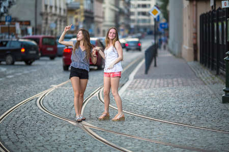 fooling: Cute young girls are fun fooling around in the middle of the streets of the old town. Stock Photo