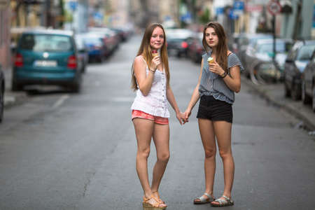 ice cream stand: Two teen girls with ice cream stand on the street holding hands.