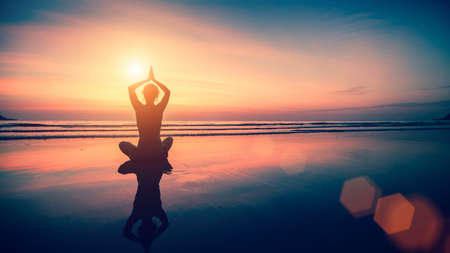 meditation woman: Silhouette meditation girl on the background of the sea and sunset. Yoga and healthy lifestyle. Stock Photo