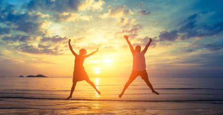 happy asian people: Silhouettes of happy young couple jumping on the ocean beach in the rays fantastic sunset. Stock Photo