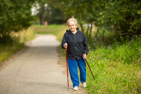 An elderly woman practices Nordic walking outdoors.