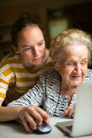 computer help: Young girl teaches elderly woman working on the computer. Granddaughter with her grandmother near the computer.