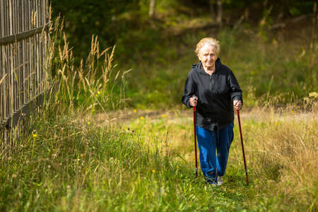 seniors walking: Mature woman engaged in Nordic walking outside the city.