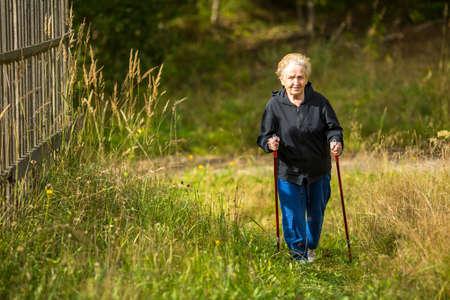persona caminando: Mujer madura que participan en la marcha nórdica fuera de la ciudad.