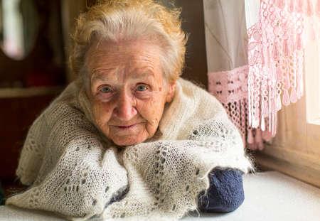 Portret van een oudere vrouw in de buurt van het raam.