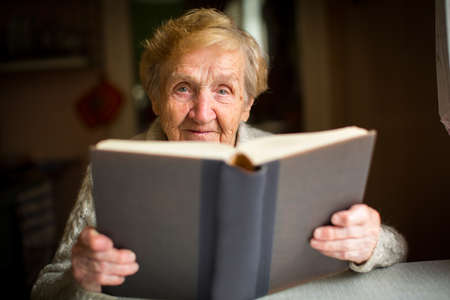 An elderly woman reading a big book sitting at a table in the house.