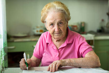 notices: Elderly senior woman populates handle her utility bills notices, sitting at the table in the kitchen.