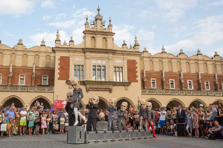 pl: KRAKOW, POLAND - JUL 12, 2015: Participants at the annually (Jul 9-12) 28th International Festival of Street Theatres - Teatr KTO (PL) Peregrinus in Main Square and at random points around the city.