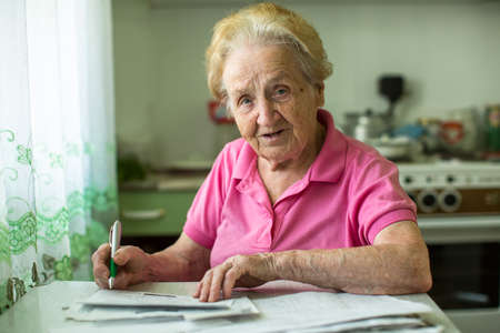 utility payments: Senior woman populates handle her utility bills notices, sitting at the table in the kitchen. Stock Photo