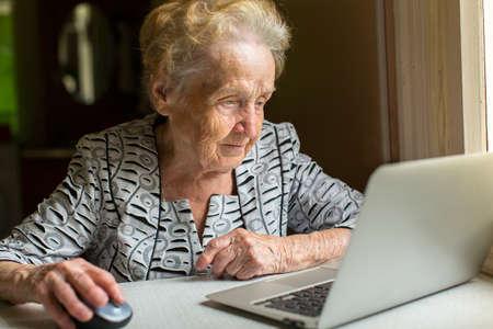 Een oudere vrouw werkt op een laptop. Stockfoto