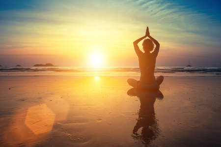 Young woman practicing yoga on the beach at amazing sunset (with reflection)