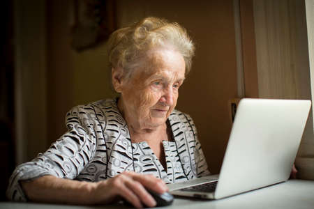 Old woman sitting with laptop at table in his house.