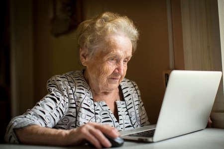 jubilados: anciana sentada con el portátil en la mesa en casa.