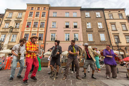 annually: KRAKOW, POLAND - JUL 12, 2015: Participants at the annually (July 9-12) 28th International Festival of Street Theatres - Orchestre International du Vetex (BelgiumFrance) in the Main Square of Krakow.