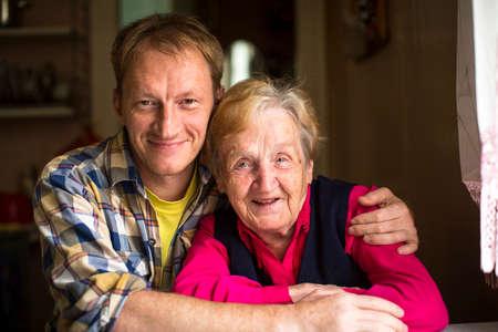 Portrait of happy elderly woman with adult grandson.