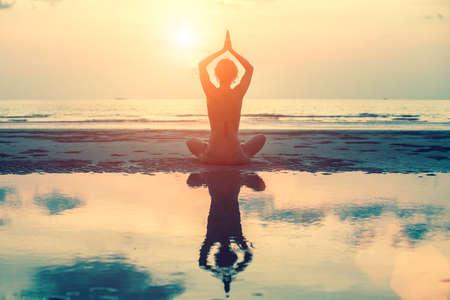 paz interior: Silueta femenina en el yoga con reflejo en el agua, actitud de la meditaci�n en el impresionante puesta de sol.