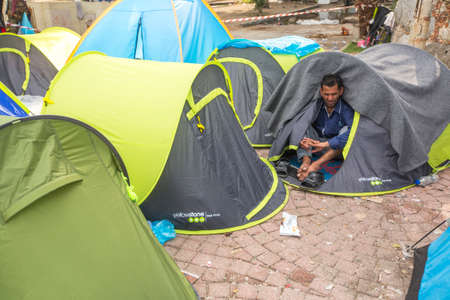 war refugee: KOS, GREECE - SEP 27, 2015: Unidentified war refugee near the tents. More than half are migrants from Syria, but there are refugees from other countries - Afghanistan, Pakistan, Iraq, Iran, Mali, Eritrea, Somalia. Editorial