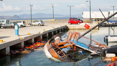 sunken boat: KOS, GREECE - SEP 27, 2015: Life Jackets discarded and sunken Turkish boat in the port. Kos island is located just 4 kilometers from the Turkish coast, and many refugees come from Turkey  in an boats.