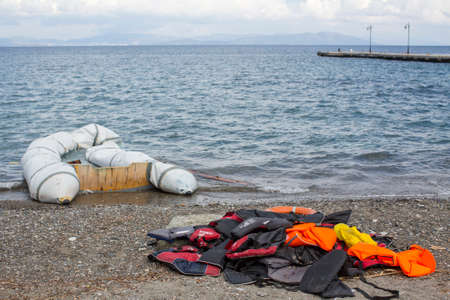 28: KOS, GREECE - SEP 28, 2015: Life Jackets discarded on a beach. Kos island is located just 4 kilometers from the Turkish coast and refugees come from Turkey in an inflatable boat.